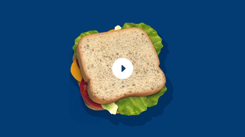 Un sandwich avec de la laitue, du fromage, de la tomate, du ketchup, de la moutarde entre deux tranches de pain.
