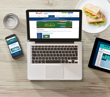 On top of a wooden table are a laptop with PlayOLG on the screen, a mobile phone with PlaySmart.ca on the screen, a tablet showing a Blackjack Strategy Card, a glass of water and a sandwich.