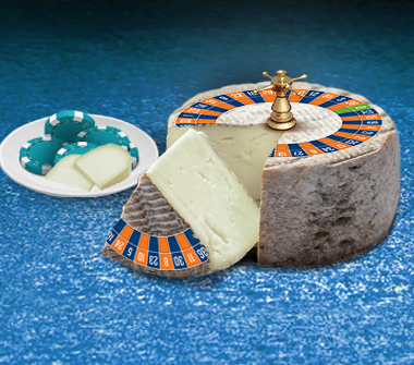 Plate of casino chips and cheese, beside roulette wheel in the shape of a cheese wheel.