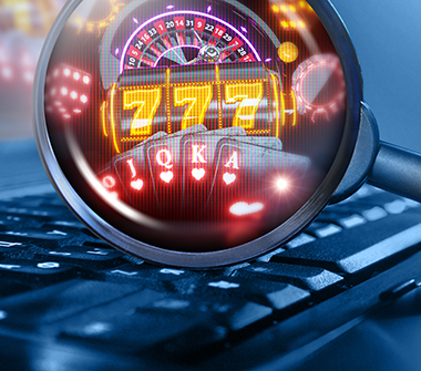 A laptop shows a magnifying glass zooming in on digital casino imagery.