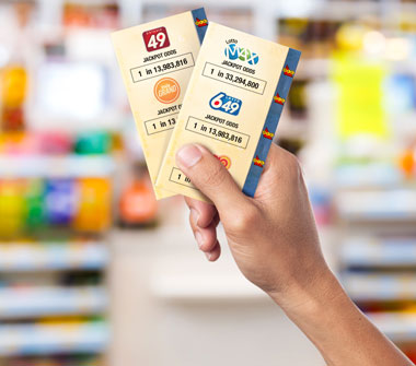 A hand holds up two lottery tickets. Printed on these tickets are the jackpot odds for some popular lotteries. The ticket on the left displays the jackpot odds for ONTARIO 49 being 1 in 13,983,816 on the top third of the ticket. The ticket on the right displays the jackpot odds for LOTTO MAX being 1 in 33,294,800 on the top third of the ticket. In the mid-section of the ticket on the right, the jackpot odds for LOTTO 6/49 are 1 in 13,983,816.